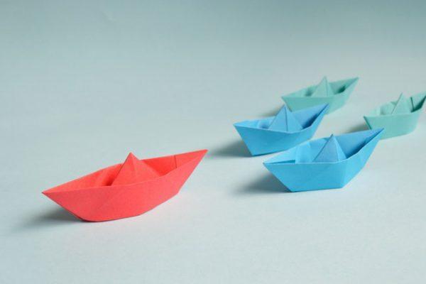 Das Bild zeigt Schiffe, das fordere rote Schiff gibt die Führung an. Lean Leadership