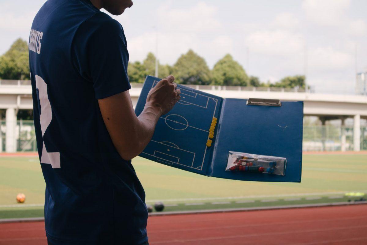 Ein Trainer mit einem Spielplan.