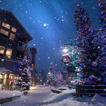 Weihnachtlicher Straßenzug in einer Stadt mit geschmückten Weihnachtsbäumen und Schnee.